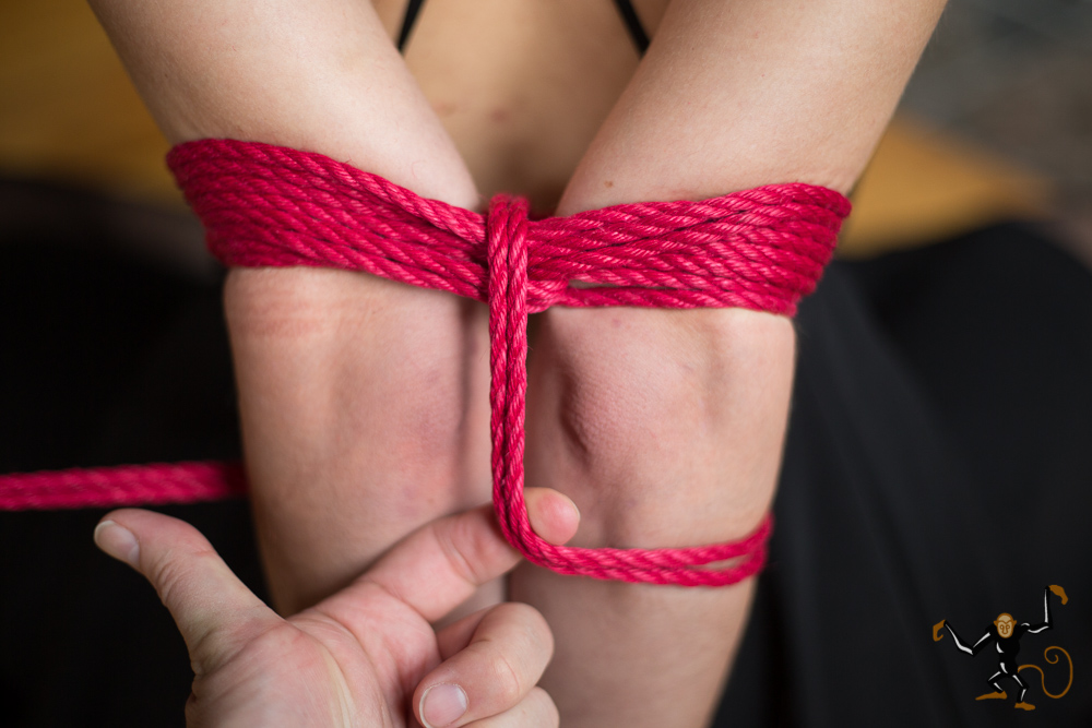 "Step 6 - Pick a spot just below the elbows to start a ""ladder tie"" element. Go left or right, it doesn't matter. Holding a finger to stabilize the rope as shown may be helpful."